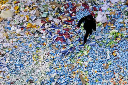 This picture taken on March 14 shows a Chinese policeman walking across a pile of fake medicines seized in Beijing in recent months, which were later destroyed.  The rapid growth of Internet commerce has led to an explosion of counterfeit drugs sold around the world, with China the biggest source of fake medicines, pharmaceutical experts said as the illicit trade is now believed to be worth around 75 billion USD globally, with criminal gangs increasingly using the web to move their products across borders.     CHINA OUT      AFP PHOTO