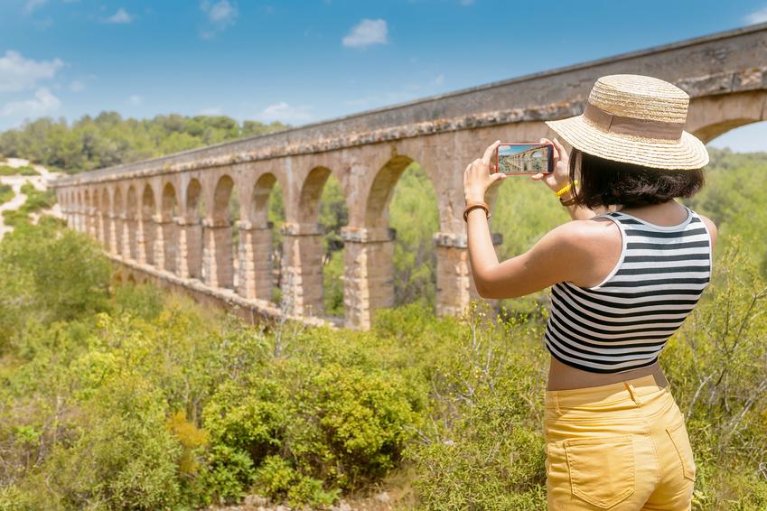 Happy young traveler taking selfie with roman Aqueduct Pont del Diable near Tarragona