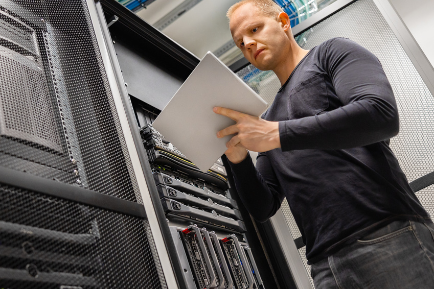 Confident male IT engineer using digital tablet standing in datacenter and monitoring servers and network.