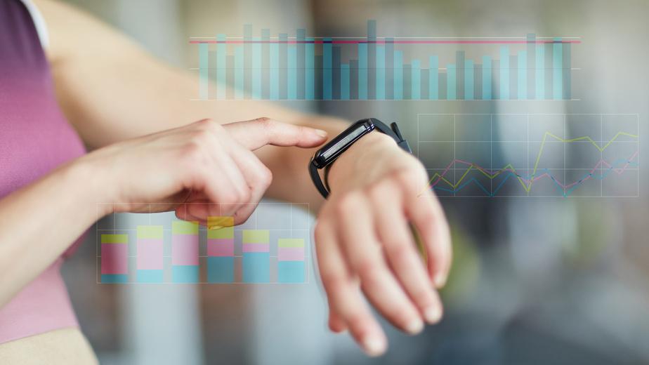 Frau kontrolliert Messwerte an Smart Watch bei Cardiofitness
